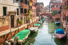 Boats and motorboats on a canal in Venice Stock Photo