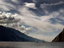 Boats on mountain lake. Partly cloudy sky over a mountain lake with sailboats. Lake Garda, Italy stock photography