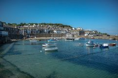 Boats in Mousehole harbour Cornwall England United Kingdom. Clear blue water in a village of Mousehole on a sunny summer day Royalty Free Stock Images
