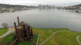 Gasworks Park Lake Union Seattle Waterfront Downtown Skyline. Boats move along vintage designed machinery lakeside on Lake Union in Seattle stock video
