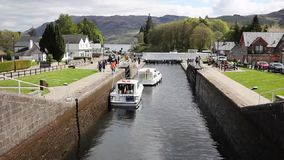 Boats moving through the lock gates on the Caledonian Canal Fort Augustus Scotland UK which connects Fort William to Inverness pas stock video