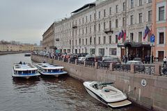 Boats near the hotel promenade on river Moika Royalty Free Stock Photos