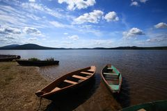Boats near lake. Image of lake with mounts at the horizon and some boats on the shore stock images