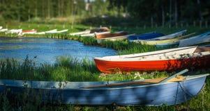 Rowboats at lake shore. Colorful rowboats at quiet lake shore in summer Stock Images