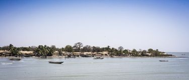 Boats on the North shoreline of the River Gambia at Barra royalty free stock photo