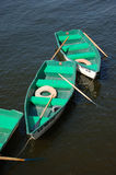 Boats With Oars. Green boats with oars floating on water Stock Photography