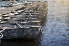 Boats with oars at a walking station. Summer rest. A long row of pleasure boats with oars on the river Stock Photo