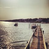 Boats off Dock (Cape Cod). Long dock in Cape Cod at Sunset, with two boats Royalty Free Stock Photo