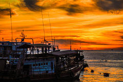 Boats in orange sky. Fisherman Boats in the ocean on evening with orange sky stock photos