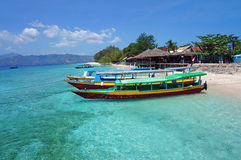 Boats parked along Gili Menos Shoreline. Indonesian boats parked along the shoreline of Gili Meno Island. Beach with white sand and crystal clean turquoise water Stock Images