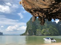 The boats are parked on a deserted clean beach against the backdrop of hanging unique rocks of the island of Thailand on a clear royalty free stock image