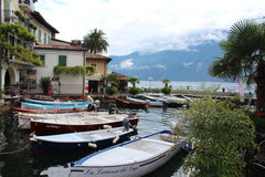 Boats parked in the Italian Lake Garda, under the mountains. In the historic city Limone Royalty Free Stock Image