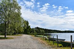 Boats parked by the lake`s shore. Along the stony pathway with lots of trees royalty free stock image