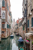 Boats parked near shabby buildings on a narrow Venetian canal. Stock Photography