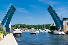 Boats passing by the Bridge in the up position on a bright sunny stock image