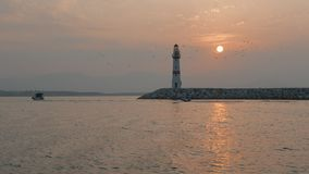 Boats passing lighthouse with rising sun at stock footage