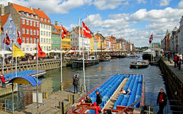 Boats and people in Nyhavn in Copenhagen. Nyhavn in Copenhagen. Old houses, boats, flags and people a sunny day Stock Images