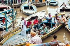 Boats and people at Triveni Ghat on the banks of the river Ganges Royalty Free Stock Image