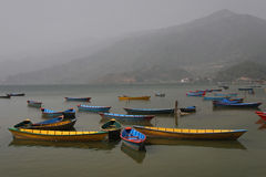Boats on Phewa lake. Blue and yellow boats on Phewa Lake in Pokhara Royalty Free Stock Image