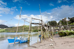 The boats and the pier. Some fishing boats at the end of their piers Royalty Free Stock Image