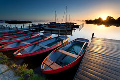 Boats by pier at harbor during sunrise Stock Image