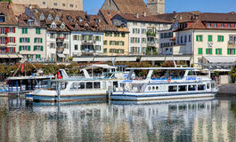 Boats at pier in Rapperswil, Switzerland. Rapperswil, Switzerland - 8 September, 2015: boats at pier on Seequai quay with old town buildings in the background royalty free stock photo