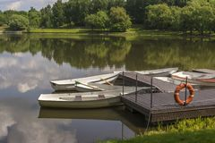 Boats at the pier on a small river. The lifeline hangs on the dock stock photography