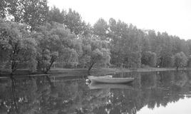 Boats on the pond. Two boats on the water, a pond surrounded by trees Stock Images