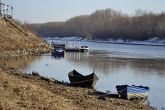 Boats and pontoons on the river Borcea. Borcea River at km 95 near the town of Calarasi. It shows the town park, boats, pontoons and willow forest with snow on royalty free stock image