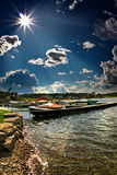 Boats in the port. With sun shining over the water and visible sun rays Stock Image
