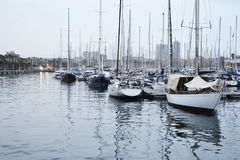 Boats in the port of Barcelona. Nice picture of the mediterranean sea in Catalonia, Spain. Several types of sailboats are seen and reflected in the water on a stock photography