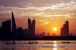 Boats in queue and Bahrain skyline at sunset Stock Photos