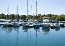 Boats reflected. Boats and masts reflected in brilliant blue lake Stock Photography