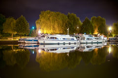 Boats reflected in France Canal in middle of the night. Reflection of luxury boats parking in silence night Stock Photo