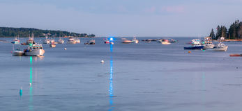 Boats reflecting light in the harbor at dusk. Boothbay Harbor boats reflected in the water at dusk Royalty Free Stock Image