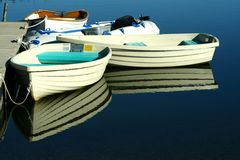 Boats with a Reflection. Small boats are reflected in the water around the dock Royalty Free Stock Image
