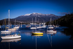 Boats and Reflections in Lindisfarne, Hobart, Tasmania, Australia. In winter with view on Mount Wellington covered in snow Stock Photo