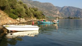 Boats with reflections. White boat with Turkish flag and turquoise boat with colorful stuff inside in the sea with reflections and mountain on background in Stock Photography