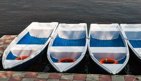 Boats for rent in a raw on a lake.  Stock Photo