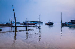 Early morning sketch by the foggy lake with boats royalty free stock images