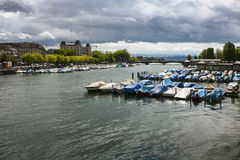 Boats on the Limmat river in Zurich, Switzerland with stormy clouds in the background Royalty Free Stock Image