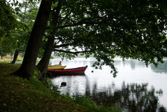 The boats in the river under the trees. Rainy summer day in Lithuania, Trakai Royalty Free Stock Photography