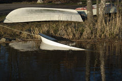Boats. Rowboats in winter storage at shore of a river. Sunk boat in foreground Royalty Free Stock Photo