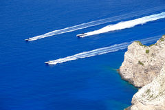 Boats rushing at high speed in clear water near the cliff of Zak Stock Photos