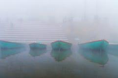 Boats on sacred river Ganges at cold foggy winter morning. Varanasi. Uttar Pradesh, India stock photo
