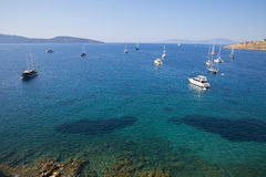 Boats, sailboats and yachts are on the way out to deep blue sea near Mediterranean sea coast. View on sea and lots of ships Stock Images