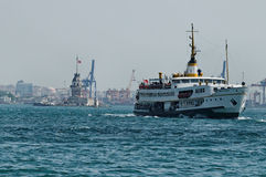 Boats sailing in Bosphorus Straight. With old lighthouse and city of Istanbul in background, Turkey Stock Image