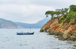 Boats sailing in a calm blue sea water near mountains in Turkey.  Stock Photography