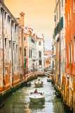 Boats sailing in water canal with orange buildings Royalty Free Stock Images