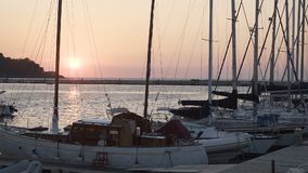 Boats for sale or rent docked at marina, beautiful sunset on horizon, seascape. Stock footage stock footage